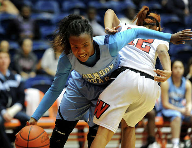 Johnson's Gabbi Bowie (4) dribbles past Wagner's Aundrea Davis (12) during a UIL 5A girls bidistrict playoff  basketball game between Johnson and Wagner at the UTSA Convocation Center in San Antonio on Monday, Feb. 13, 2012. Photo: JOHN ALBRIGHT, For The Express-News / Special to the Express-News