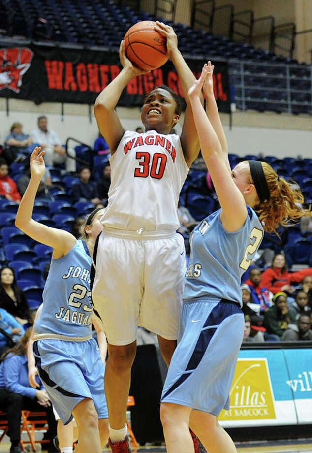 Wagner's Tesha Smith shoots between Johnson's Bailey Ulrich (right) and Katie Burcham during a Class 5A bidistrict game Monday at the UTSA Convocation Center. The Thunderbirds pulled out a 59-58 double-overtime victory to eliminate the Jaguars, with Smith making the game-clinching defensive play. Photo: JOHN ALBRIGHT, For The Express-News / Special to the Express-News