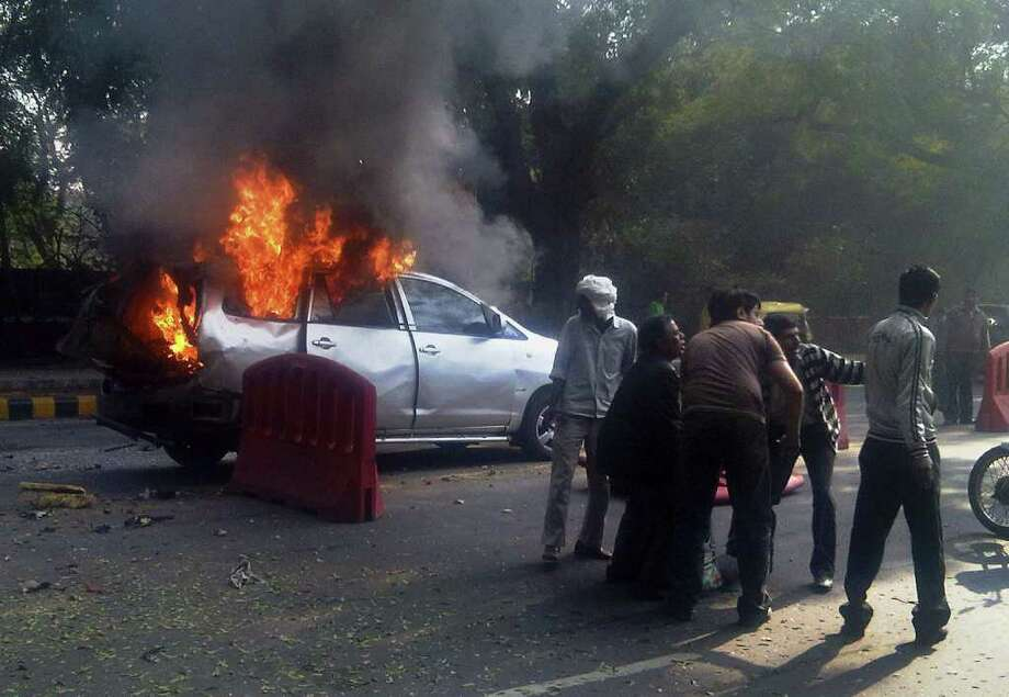 ALTERNATE CROP TO DEL847- An injured person is carried from a burning car belonging to the Israeli Embassy as it is in flames after an explosion, in New Delhi, India, Monday, Feb. 13, 2012. The wife of an Israeli diplomat was injured in the explosion, the same day as an Israeli Embassy staffer in Georgia found a bomb underneath his car, which was dismantled before exploding, according to Indian and Israeli media reports. (AP Photo/Joji Thomas, Economic Times) INDIA OUT- FULL CREDIT MANDATORY Photo: Joji Thomas / Economic Times