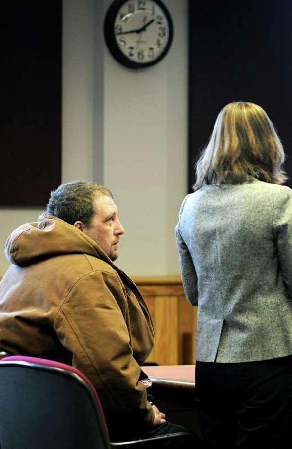 Timothy Bernaby, left, of Hartland looks to his public defender Jordana Levine during his arraignment in Windsor District Court in White River Junction, Vt. Monday, Feb. 13, 2012. Bernaby pleaded not guilty Monday to a charge that he stole a number of original cards and letters written by poet Robert Frost that were in the drawer of a desk that was donated to the nonprofit agency where he worked and then sold them for more than $25,000 in cash and other goods.    (AP Photo/ Valley News, James M. Patterson, Pool) Photo: James M. Patterson