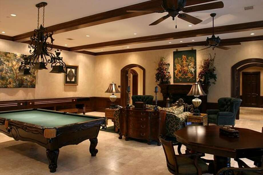 2nd Floor game room complete with shuffle board, pool table, game tables and fireplace. Entire game room opens out with 3 double doors onto a covered balcony overlooking the pool/backyard. (Coleman Realty)