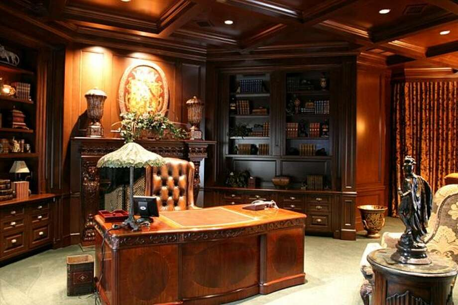 The Executive Office/Library. It's every man's dream to have a domain such as this in his own home. Magnificent custom designed fireplace and is completed with a private elevator. (Coleman Realty)