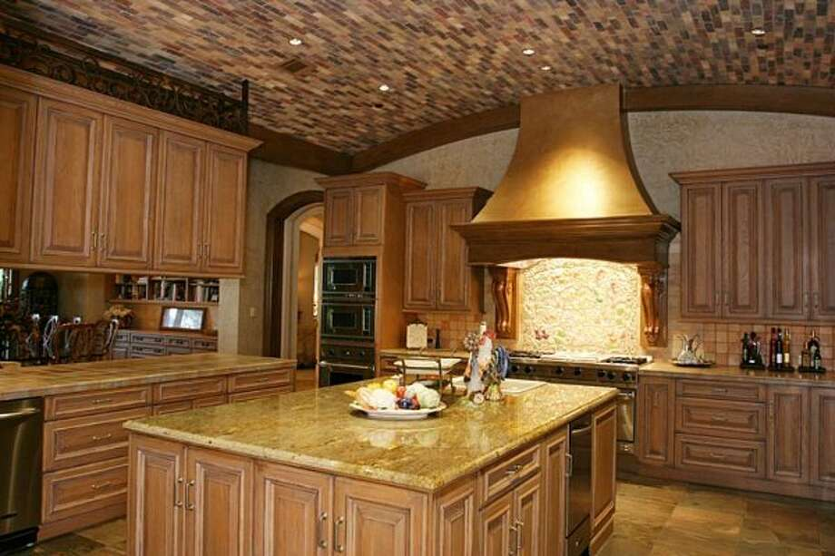 Main kitchen has a barrel ceiling, custom hand painted tiles and Murial and Wood Mode cabinets. Two side by side stainless refrigerators, ice maker, 2 dishwashers, 2 compactors and large island w/sink. Adjoining catering kitchen with walk in cooler (Coleman Realty)