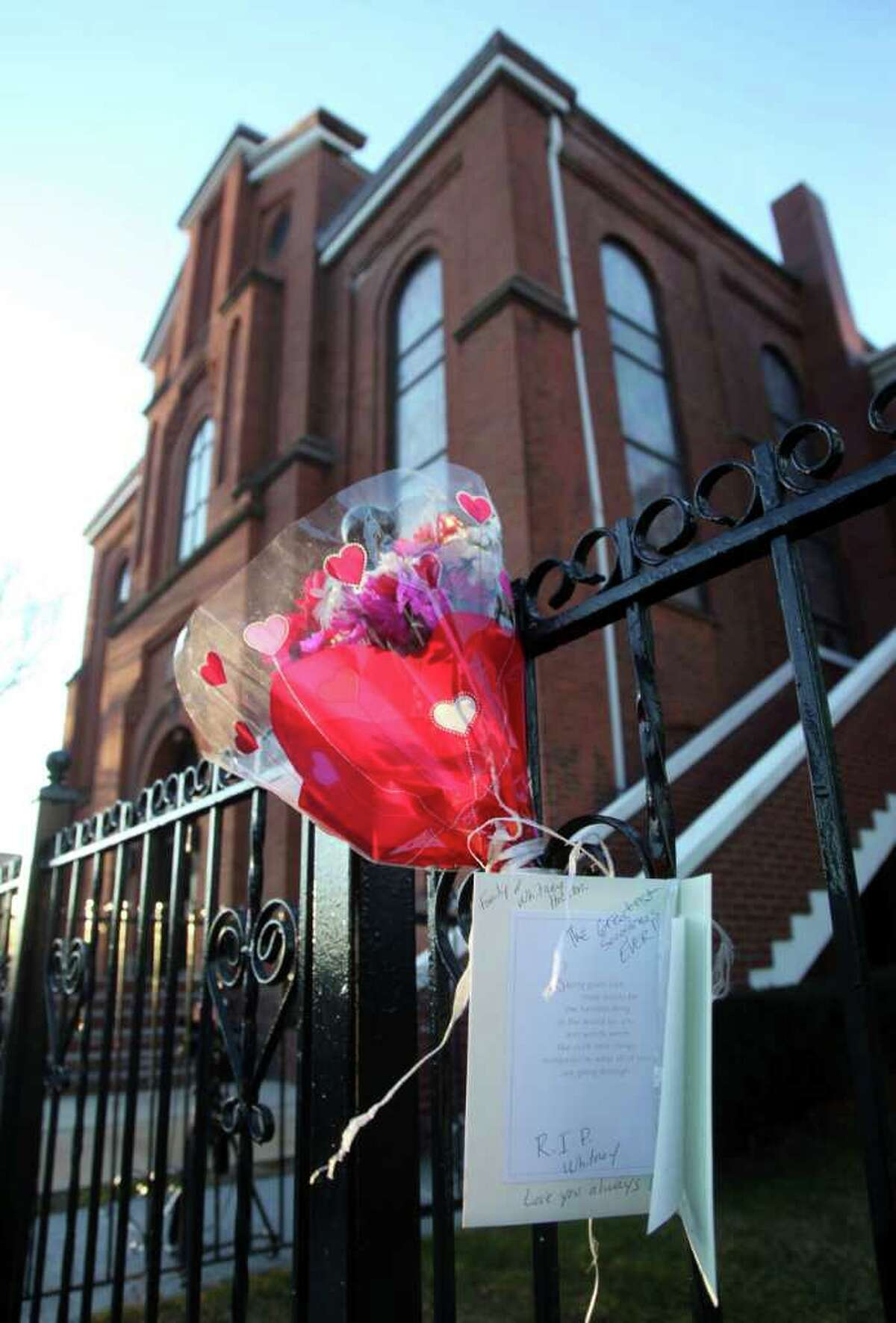 In this file photo of Sunday, Feb. 12, 2012, flowers and a card hang on a fence in front of New Hope Baptist Church in Newark, N.J. Whitney Houston's funeral will be held Saturday, Feb. 18 at the church where she sang in the choir as a girl. Houston, who ruled as pop music's queen until her majestic voice and regal image were ravaged by drug use, erratic behavior and a tumultuous marriage to singer Bobby Brown, died Saturday. She was 48.