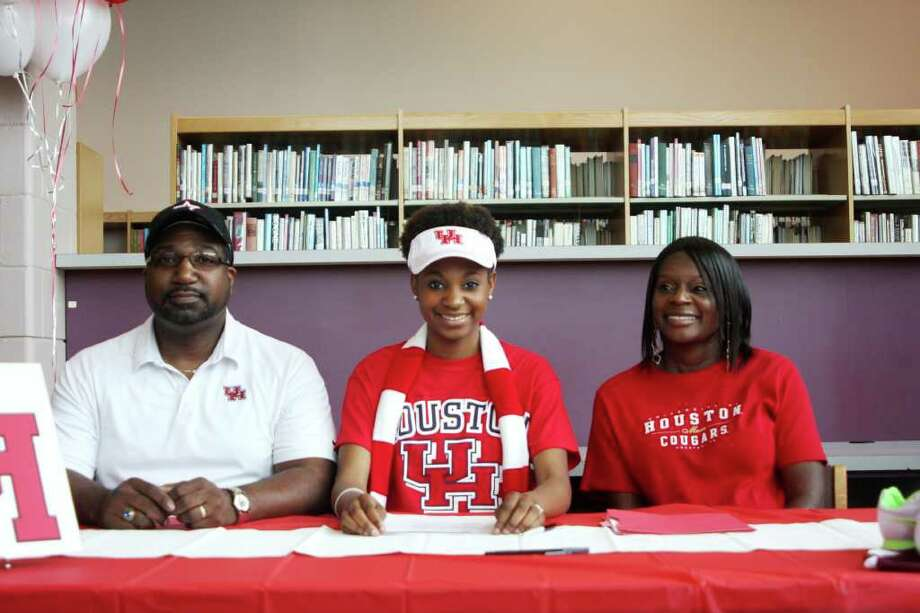 """Silsbee track star Ashley Johnson (center) signs a letter of intent to run track with the University of Houston accompanied by her parents. John holds a school record in the high jump at 5'8"""". Photo: David Lisenby, HCN_Signing"""