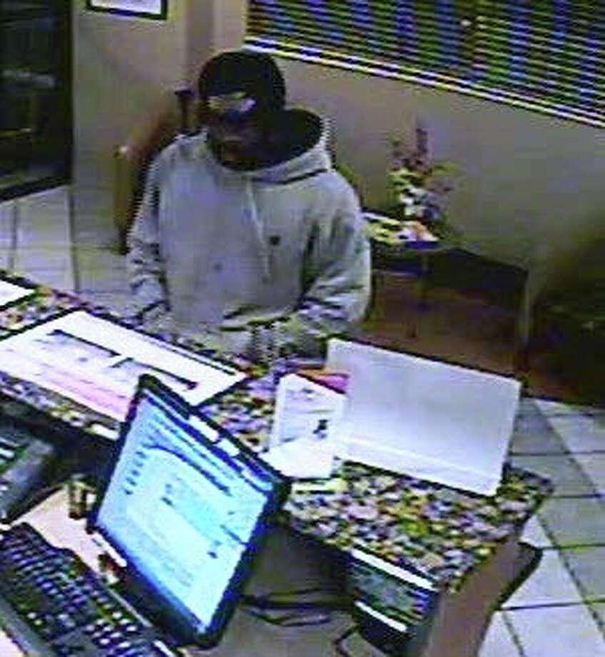 Surveillance video shows a suspect carrying out a robbery at the Red Roof Inn on Rowe Avenue in Milford, Conn. The suspect took an undisclosed amount of cash, police said. Photo: Contributed Photo