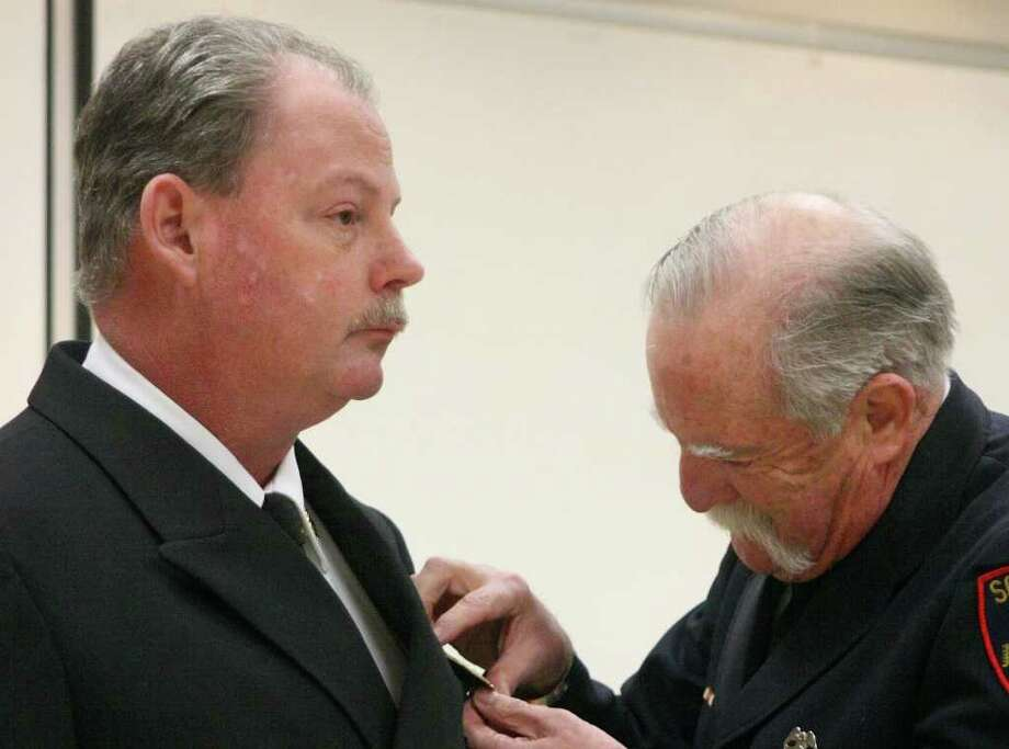 Newly elected Fire Chief Jim Philp (left) is pinned with his coller devices by his father, Ralph, who is retired from the Southfield Fire Department in Michigan. Seven promotions were celebrated at the Lumberton Fire and EMS firehouse on Feb. 11. Photo: David Lisenby, HCN_Firefighters