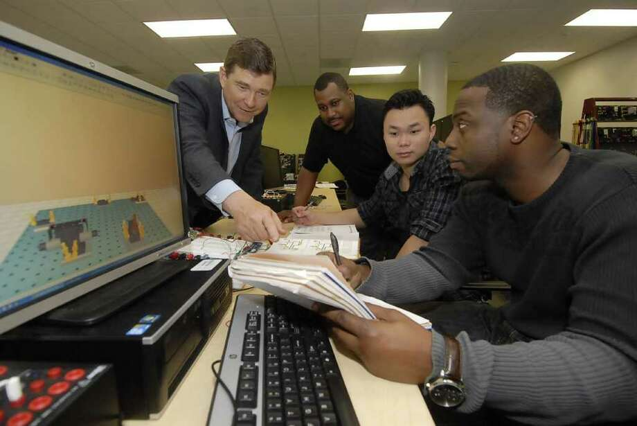 Professor Scott Nugent, left, joins professor Ron Gardner and students Hieu Le and R. C. Adams as they work on a project in their engineering tech class. Photo: Tony Bullard / Tony Bullard & the Houston Chronicle