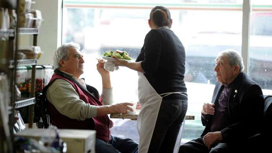 Monica Hernandez serves lunch to Domnick Agostino, left, and Frank Cavaliero, right, at L&G Italian Market on West Main Street in Stamford on Tuesday, February 14, 2012. Photo: Lindsay Niegelberg / Stamford Advocate