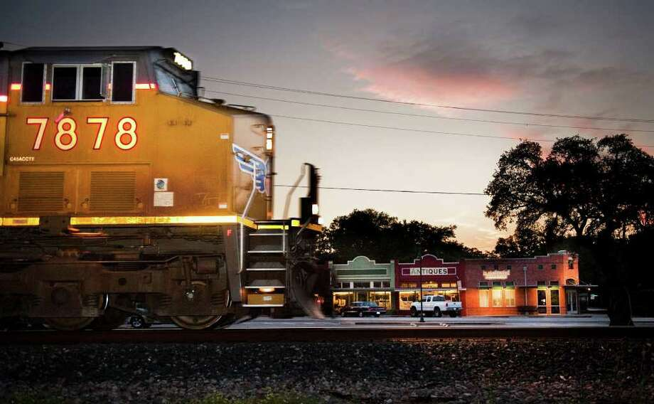 A Union Pacific Train passes down town buildings on Railroad St. in Buda at sunset. (Credit Community Impact Newspapers) Photo: Ashley Landis, Texas Hill Country / copyright 2011 Ashley Landis