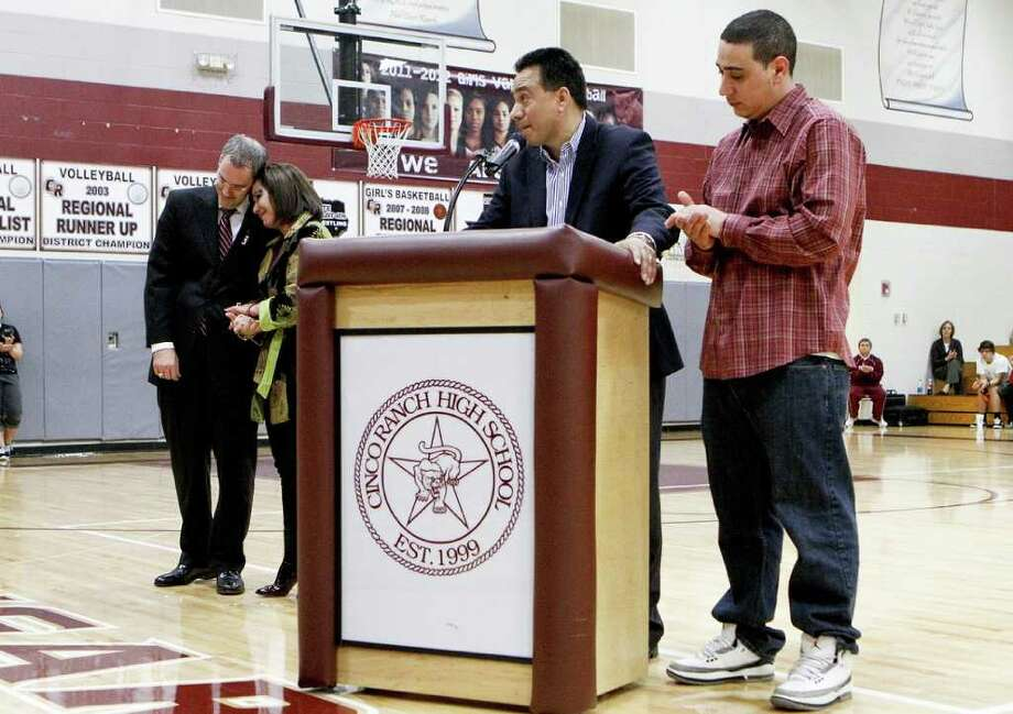 Michael Saiz, the father of Christopher Saiz, speaks to the crowd in memory of his son who was killed in a December car accident. With him are his wife, Magda, their son, Tony, and Cinco Ranch varsity basketball coach Neil King. Photo: Diana L. Porter / © Diana L. Porter