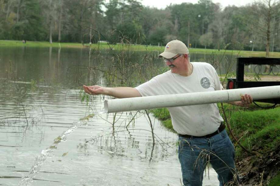 Harris County Precinct 4 Commissioner Jack Cagle releases fish into the lake at Burroughs Park as part of the restocking process. Photo: Jerry Baker