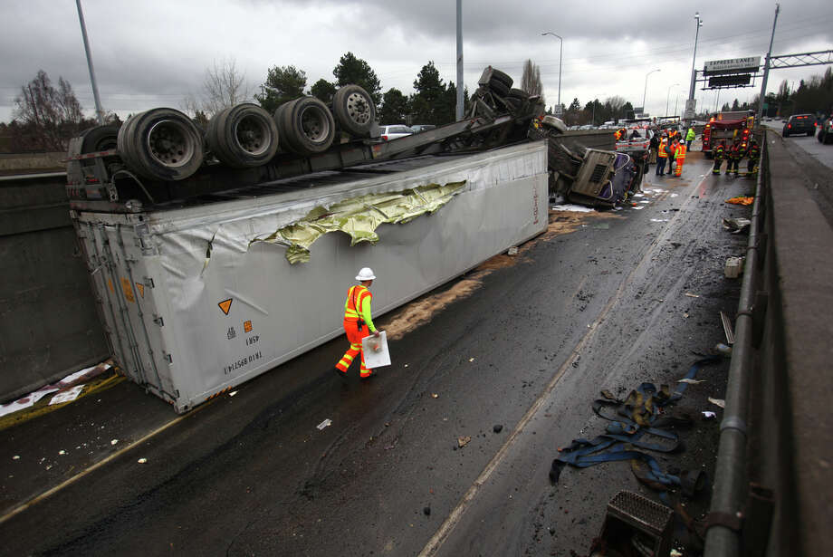 Crews work the scene after a semi truck hauling eggs was involved in an accident and drove off Interstate 5 onto the Ravenna on-ramp below.  Four people were injured in the accident and the truck's fuel tanks ruptured, spilling diesel on the roadway below. Photo: JOSHUA TRUJILLO / SEATTLEPI.COM