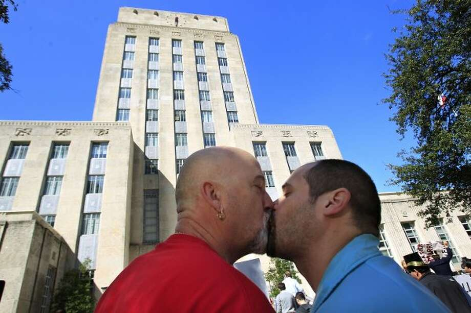 Richard McLeod, left, of Houston kisses his boyfriend of one month, Nicholas Benjamin during a rally at City Hall in support of gay marriage Tuesday, Feb. 14, 2012, in Houston.  The group of more than 30 gay couples and those in support of gay marriage gathered at the Harris County Clerks Office to apply for marriage licenses, where their requests were denied. The group then marched to City Hall to hold a short protest.  Mayor Annise Parker joined the group and gave them a proclamation. ( Johnny Hanson / Houston Chronicle ) (Houston Chronicle)