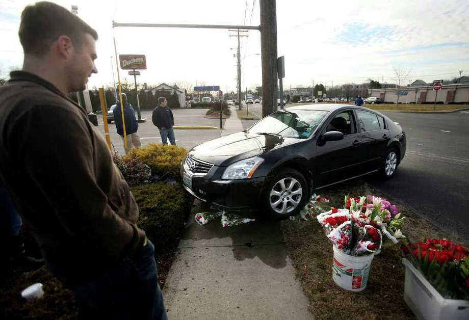 Fairfield University student Greg Jensen looks at his 2007 Nissan Maxima that was struck by another vehicle while unoccupied in the Splash car wash on the Post Road in Fairfield on Tuesday, February 14, 2012. The car travelled across multiple lanes of traffic, crashing into a Valentine's Day flower display in front of the Duchess Restaurant. Photo: Brian A. Pounds / Connecticut Post
