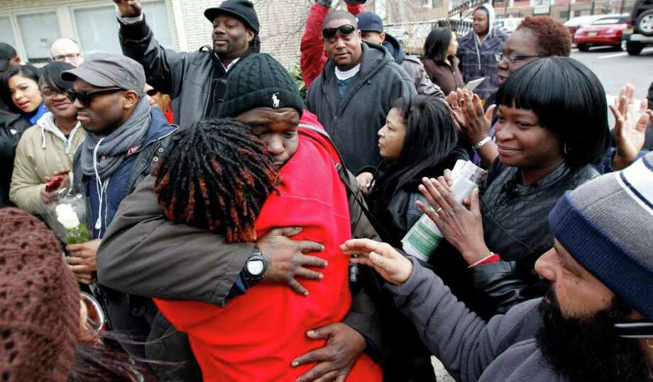 Fans of the late singer Whitney Houston comfort each other outside of Whigham Funeral Home, where the body of singer is held since its arrival in New Jersey, Tuesday, Feb. 14, 2012, in Newark, N.J. Funeral services for Houston are set for Feb. 18 at New Hope Baptist Church. Houston, who ruled as pop music's queen until her majestic voice and regal image were ravaged by drug use, erratic behavior and a tumultuous marriage to singer Bobby Brown, died Feb. 11. She was 48. (AP Photo/Julio Cortez) Photo: Julio Cortez