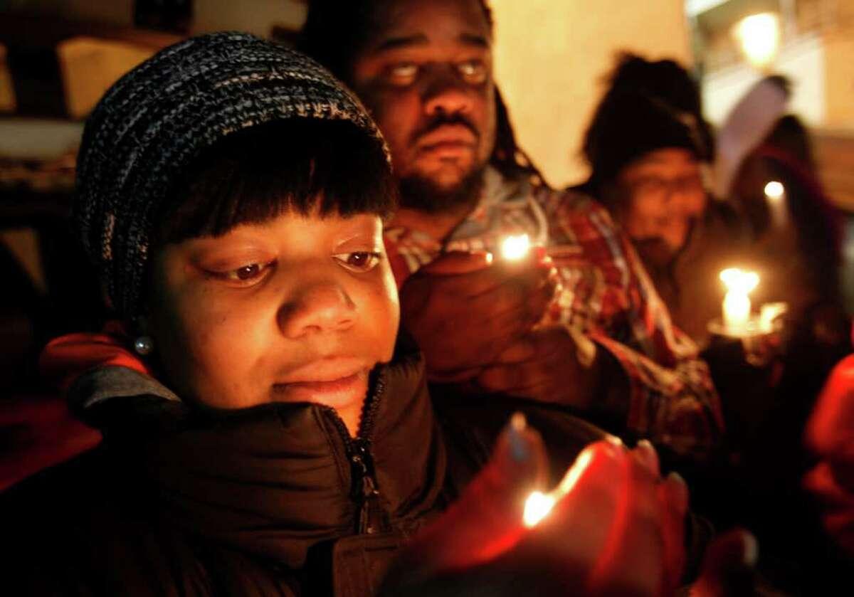 Numerosas personas participan en una vigilia en memoria de Whitney Houston mientras aguardaban la llegada del féretro con el cadáver de la artista a la Casa Funeraria Whigham en Newark, Nueva Jersey, el lunes 13 de febrero de 2012. (AP foto/Rich Schultz)