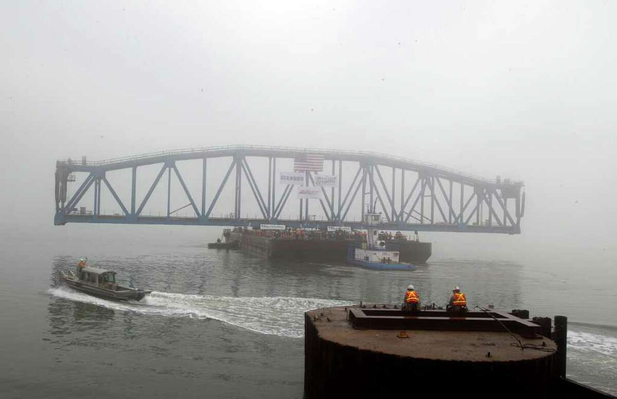 Workers wait in the fog during as the new Galveston Causeway Railroad Bridge is brought in on Tuesday, Feb. 14, 2012, in Galveston. The 382-foot bridge will replace the old 125-foot span that connects Galveston to the mainland. Construction began on the $80 million project in June of 2010 and is expected to be completed by this coming June. BNSF Railway's Regional Director og Public Affairs Joseph Faust said: