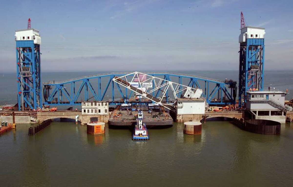 The new railroad bridge span dwarfs the old bridge span in the foreground.