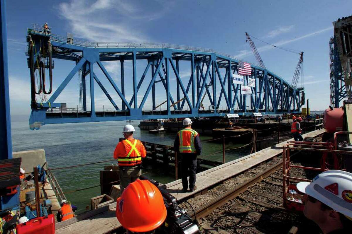 The new rail bridge span is maneuvered into place.