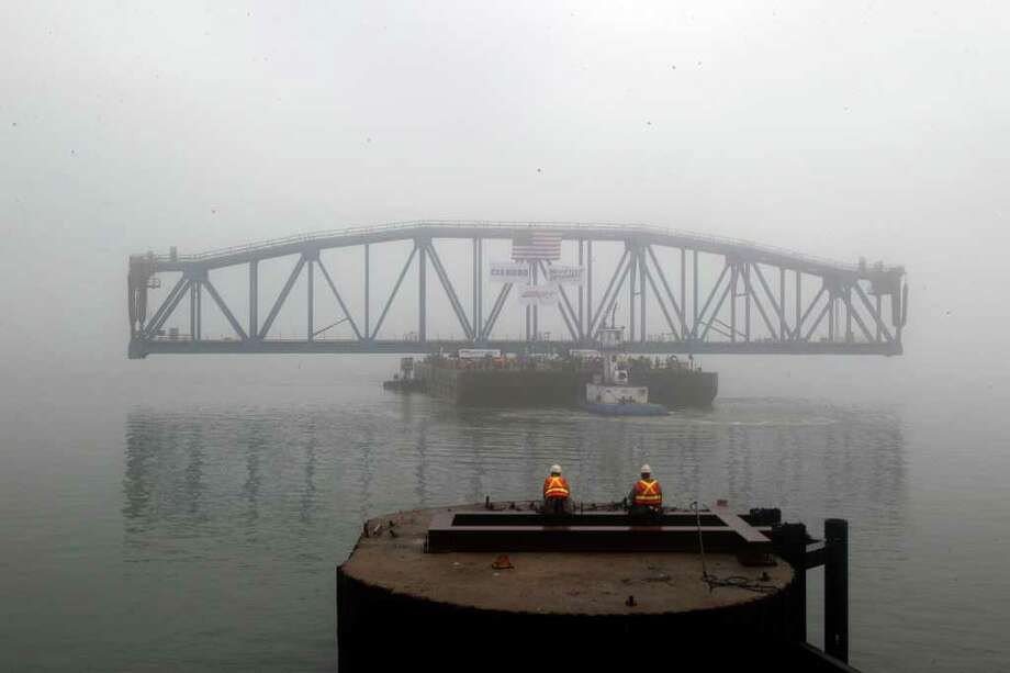 Workers wait in the fog during as the span is brought in. Photo: James Nielsen, Chronicle / © 2011 Houston Chronicle