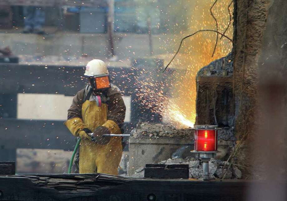 A worker cuts away a portion of the old bridge span. Photo: James Nielsen, Chronicle / © 2011 Houston Chronicle