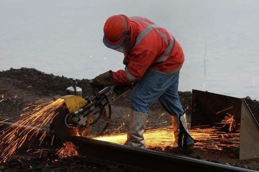 A worker cuts a rail line.