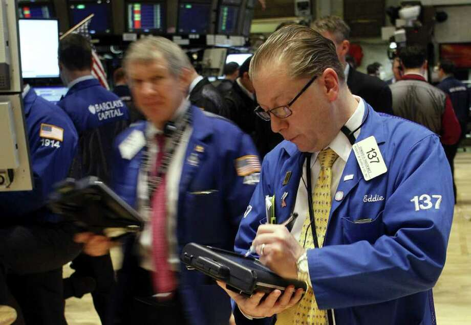 In this Feb. 13, 2012 photo, trader Edward H. Radzienwicz works the floor of the New York Stock Exchange. Another mass downgrade of the creditworthiness of European countries had little market impact Tuesday, Feb. 14, as investors continued to predict that Greece would soon get its hands on vital bailout cash to avoid a ruinous bankruptcy. (AP Photo/David Karp) Photo: DAVID KARP