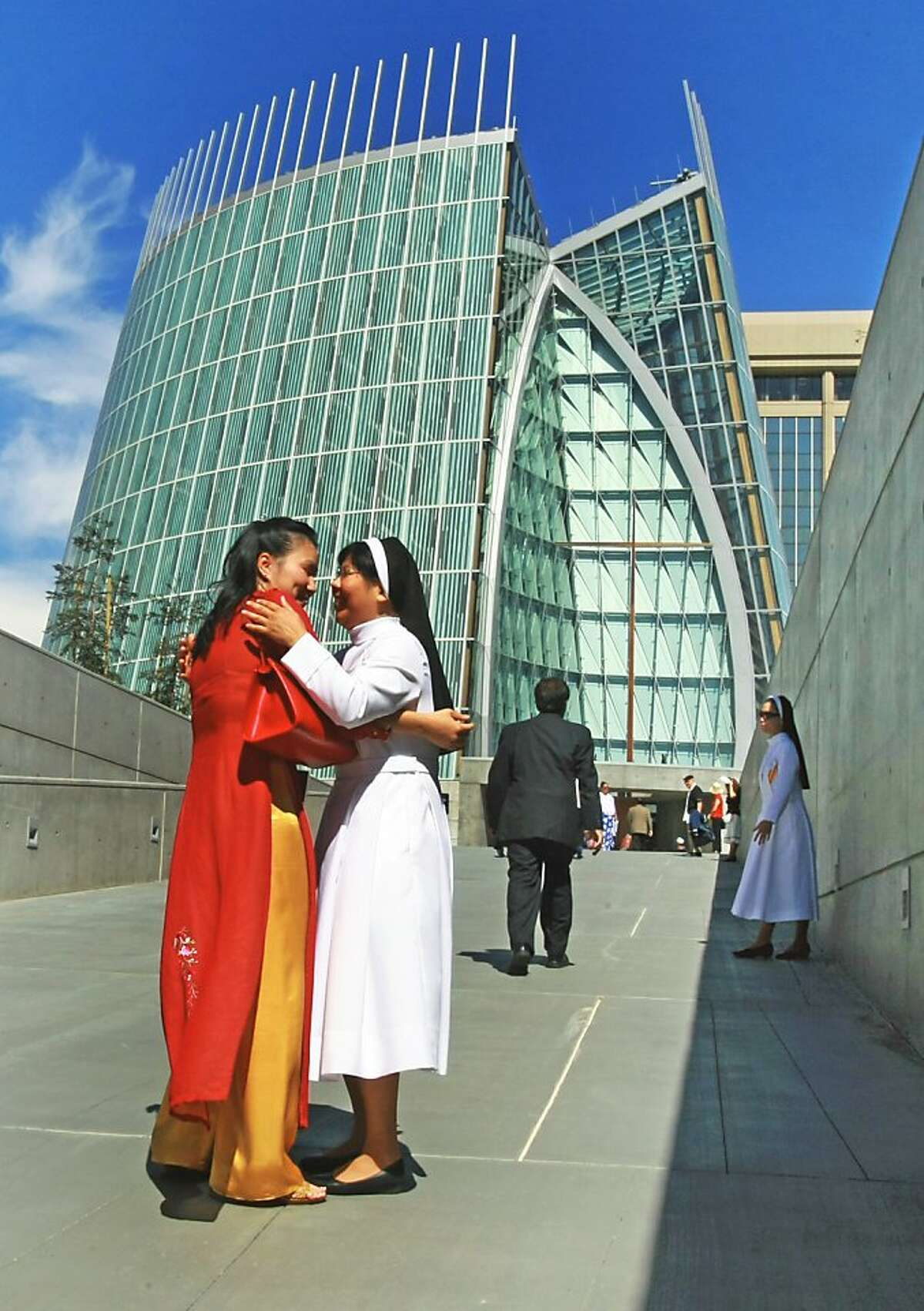 Vicki Nguyen from San Lorenso hugs Sister Christine Le from holly Cross outside the new Cathedral of Light Thursday, Sept. 25, 2008, in Oakland, Calif. Hundreds of parishioners joined priests from throughout the state and four attending Cardinals for the ceremony.