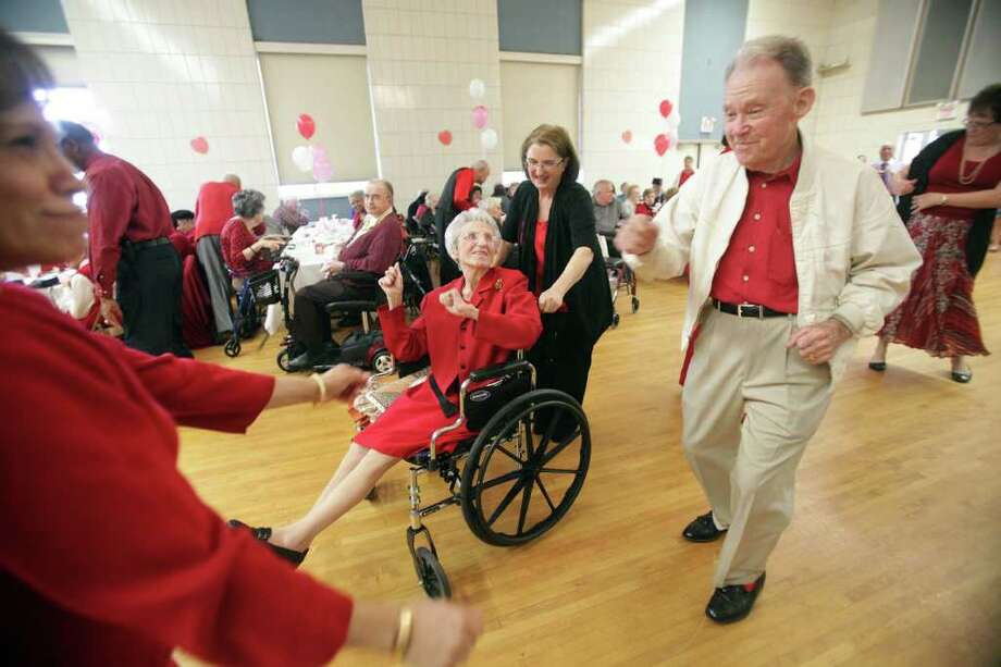 Rose Mary Spencer, 89, is wheeled around by Kathy Bingham as Rose Mary dances with her husband of 65 years Patrick Spencer, 89, during the Valentine's Day Dance at St. Dominic Village. Photo: Mayra Beltran, Houston Chronicle / © 2012 Houston Chronicle