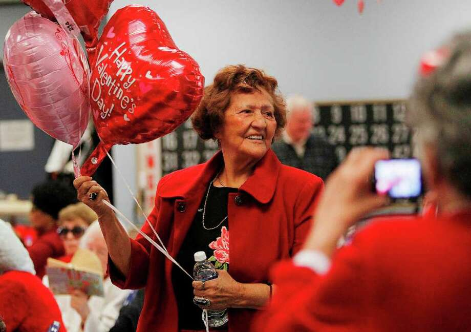 Teresa Mata shows up with balloons for her friends at the Valentine's Day Dance at the Neighborhood Center Inc. West End Senior Center. Photo: Mayra Beltran, Houston Chronicle / © 2012 Houston Chronicle