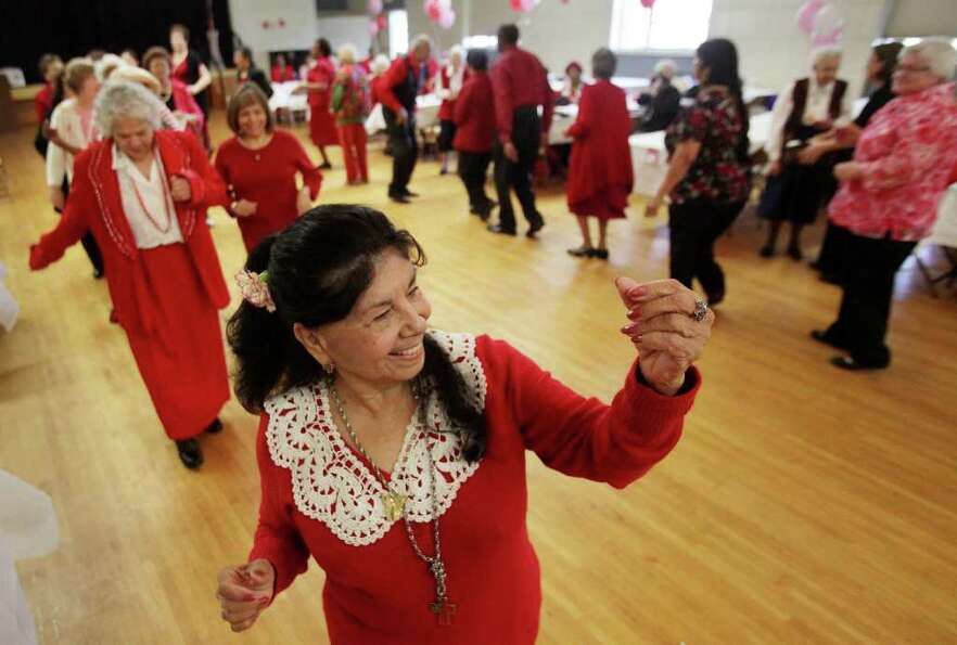 Dalia Rico, 70, dances in the conga line during the Valentine's Day Dance at St. Dominic Village.