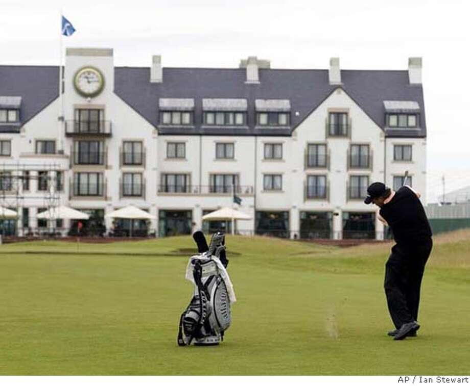 ** CORRECTS SPELLING OF SECOND NAME ** U.S. golfer Phil Mickelson plays a shot to the 18th green at Carnoustie golf course in preparation for next weeks British Open golf championship in Carnoustie Scotland, Tuesday July 10, 2007. The course's hotel is seen in the background. (AP Photo/Ian Stewart) ** CORRECTS SPELLING OF SECOND NAME ** Photo: IAN STEWART