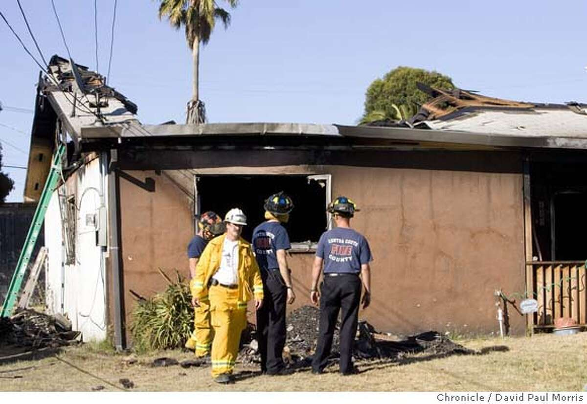 SAN PABLO, CA - JULY 21: Contra Costa County Fire Protection District firefighters look over the roof and debris from a fire that took the lives of two residents and two firefighters on July 21, 2007 in San Pablo, California. The deaths of the firefighters was the first on-duty deaths in the fire district's history, (Photo by David Paul Morris / The Chronicle) Ran on: 07-22-2007 Matt Burton, 34, was married and had two children.