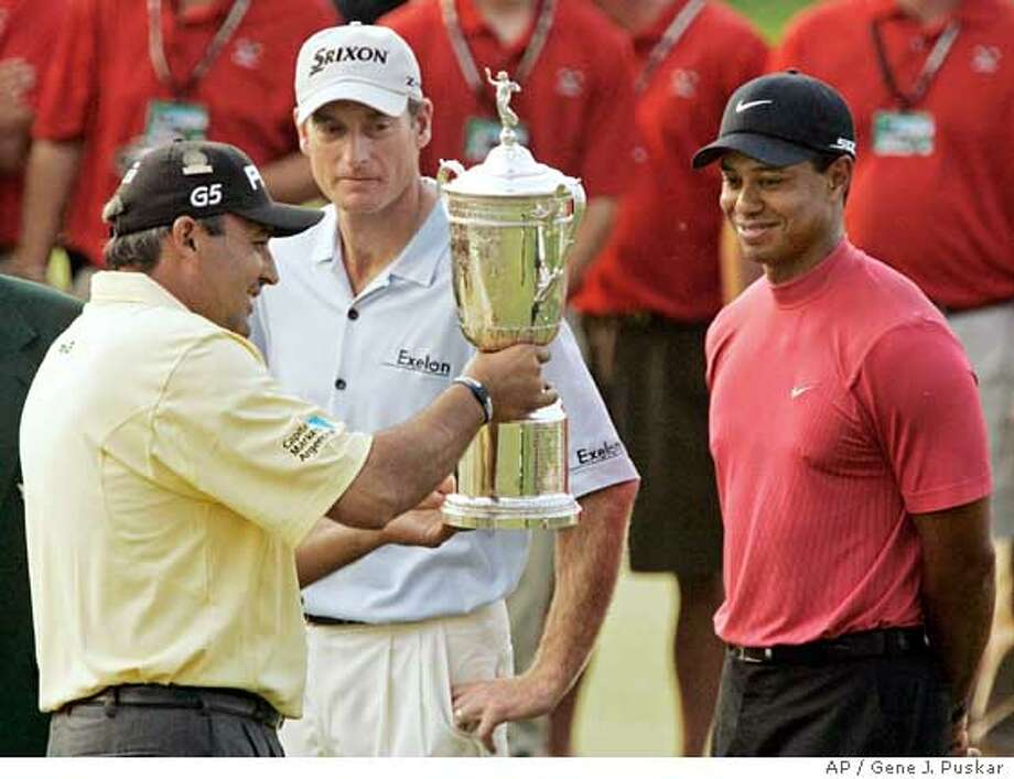 Angel Cabrera of Argentina, left, shows runners-up Jim Furyk and Tiger Woods, right, his championship trophy after winning the 107th U.S. Open Golf Championship at the Oakmont Country Club in Oakmont, Pa., Sunday, June 17, 2007. Cabrera finished the tournament 5-over-par 285. Woods tied with Furyk for second in the tournament with 6-over-par 286.(AP Photo/Gene J. Puskar) Photo: Gene J. Puskar