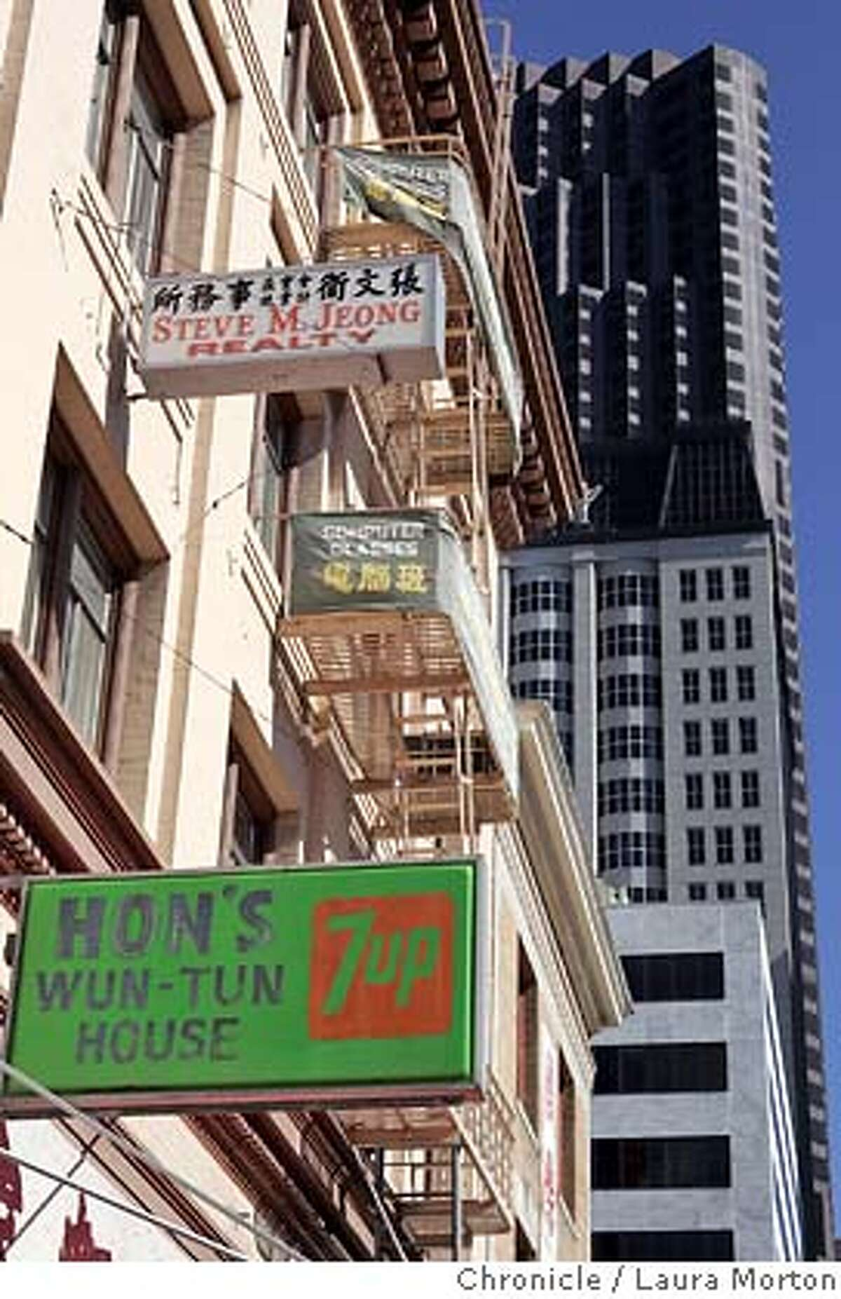 place20731_lm.JPG Signs on small buildings mix with large buildings, such as the Bank of America tower, on Kearny Street in San Francisco,CA. Laura Morton/The Chronicle MANDATORY CREDIT FOR PHOTOGRAPHER AND SAN FRANCISCO CHRONICLE/ -MAGS OUT