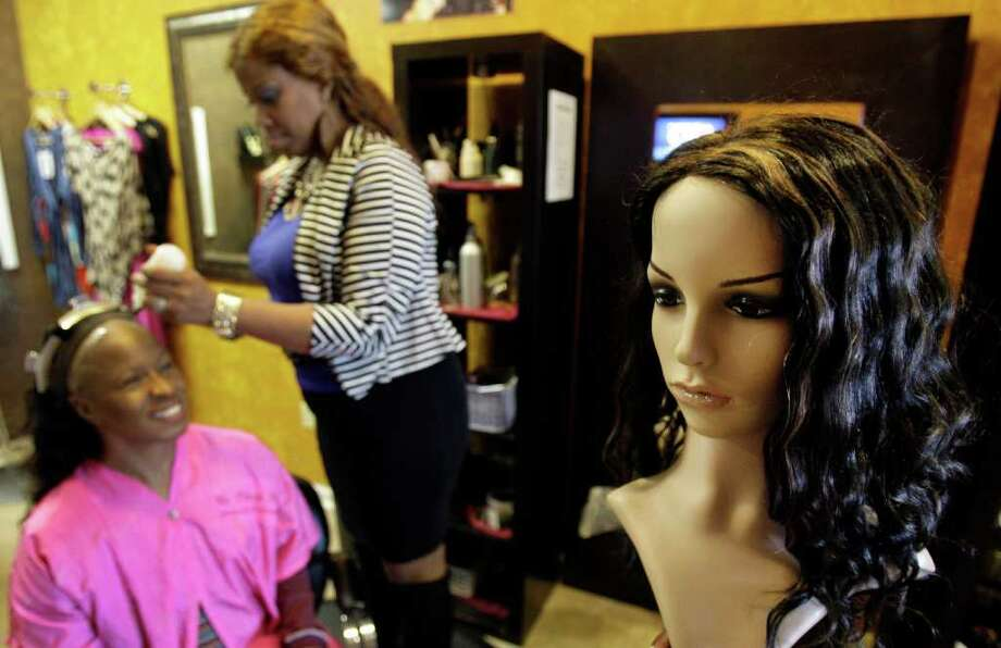 A Remy Indian hair wig is on display, right, as salon owner Lisa Amosu attends to client Gwen Jones on Tuesday at My Trendy Place, 10350 South Post Oak. Last summer, Amosu lost hair worth $150,000 to thieves. Photo: Melissa Phillip / © 2011 Houston Chronicle