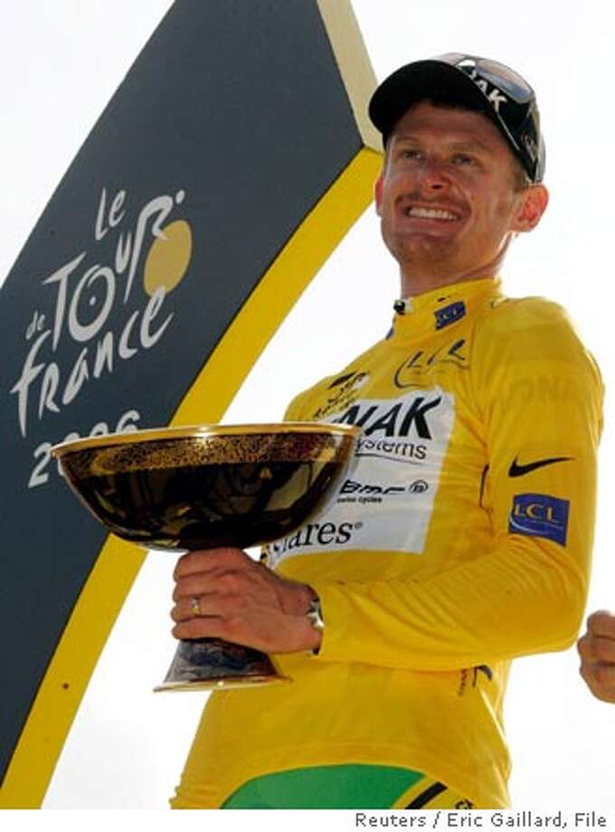 Phonak's team rider Floyd Landis of the U.S., wearing the leader's yellow jersey, holds a trophy on the podium after winning the 93rd Tour de France cycling race after the final stage between Sceaux-Antony and the Champs-Elysees in Paris, in this July 23, 2006 file photo. Tour de France winner Landis has given a positive drugs test for the male sex hormone testosterone, his Phonak team said on July 27, 2006. REUTERS/Eric Gaillard/Files (FRANCE) Photo: ERIC GAILLARD