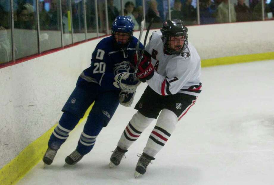 Darien's Trent Bergin and New Canaan's Paul Clemente in action as New Canaan High School and Darien face off in a boys hockey game at Darien Ice Rink in Darien, Conn., February 14, 2012. Photo: Keelin Daly / Stamford Advocate