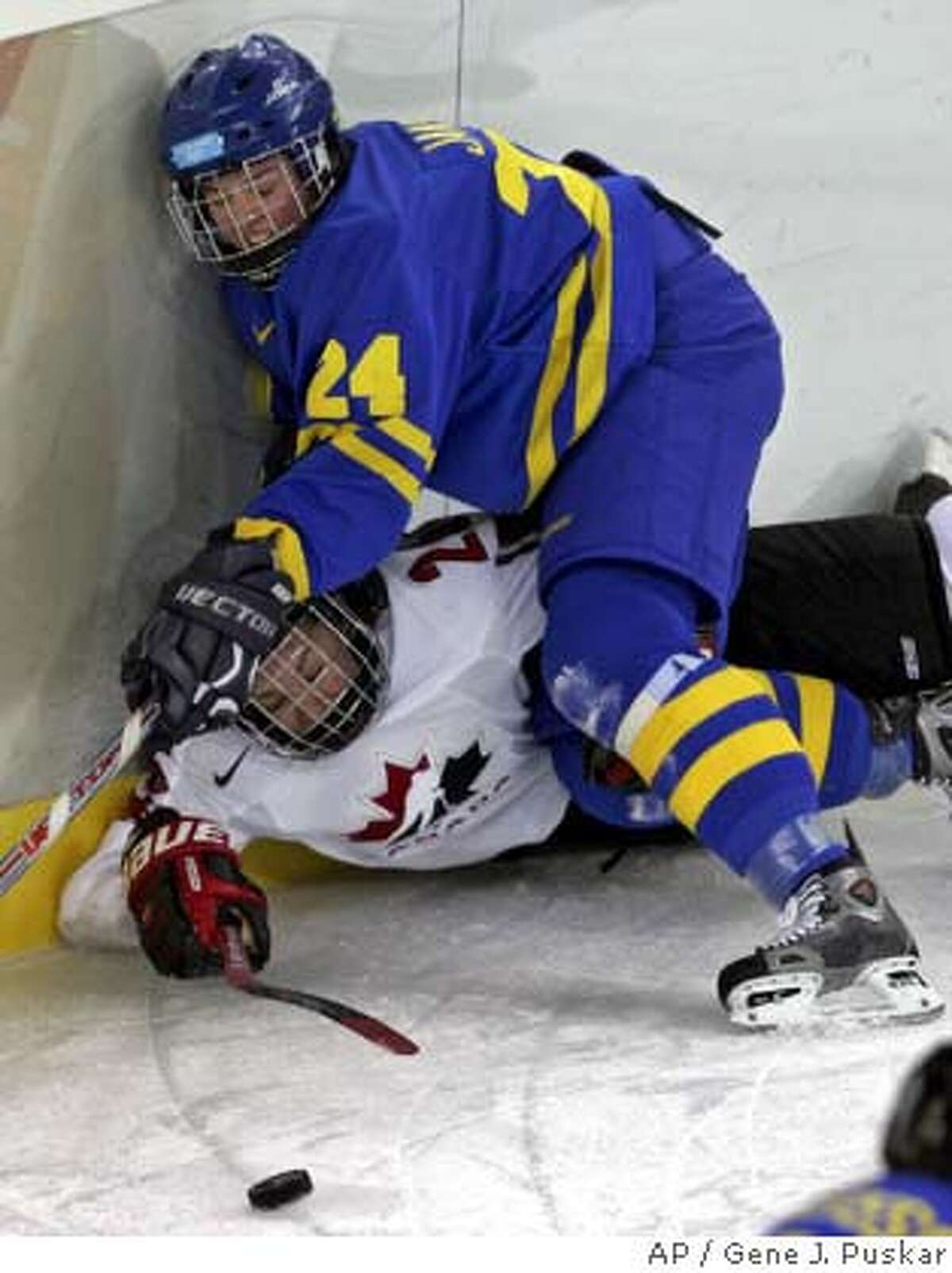 weden's Nanna Jansson (24) collides along the boards with Canada's Sarah Vaillancourt during a 2006 Winter Olympics women's ice hockey match Tuesday, Feb. 14, 2006, in Turin, Italy. (AP Photo/Gene J. Puskar)
