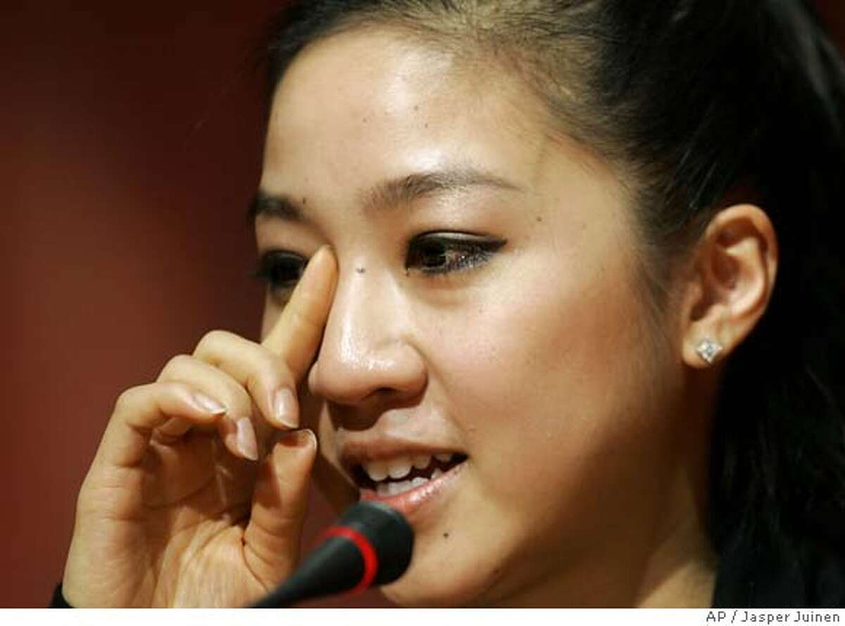 Figure Skater Michelle Kwan of the United States wipes a tear during a press conference in Turin, Italy, Sunday Feb. 12, 2006. Kwan spoke about her withdrawal from the games due to a groin injury. (AP Photo/Jasper Juinen)