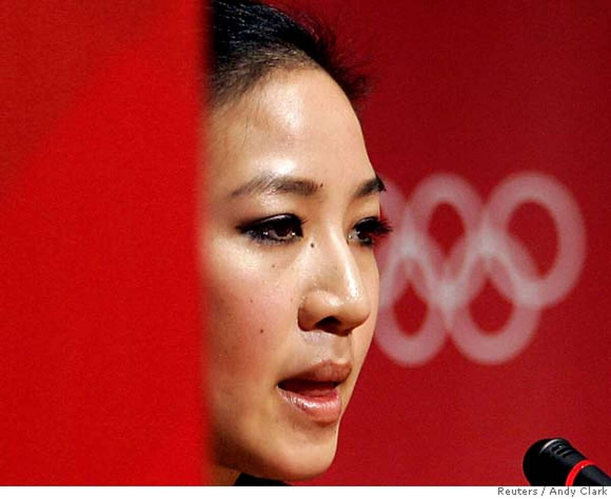 Figure skater Michelle Kwan of the U.S. listens to a question during a media conference after pulling out of the Torino 2006 Winter Olympic Games in Turin, Italy February 12, 2006. Kwan, a five-time world champion, sustained a groin strain during practice on Saturday. REUTERS/Andy Clark 0