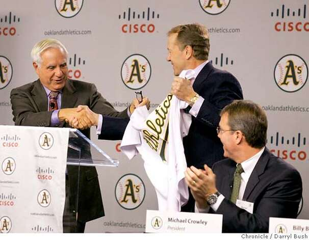 "Athletics Co-owner and Managing partner, Lew Wolf shakes hands with Cisco Chief Operating Officer, John Chambers, right center, as A's president, Michael Crowley, right, looks on while they display a new Athletics jersey with ""Cisco,"" written on it, fat an Oakland Athletics press conference at Cisco Systems in (cq) in San Jose, CA, on Tuesday, November, 14, 2006. 11/14/06  Darryl Bush / The Chronicle ** Lew Wolf, John Chambers, Allan H. (Bud) Selig, Michael Crowley (cq) (cq) Photo: Darryl Bush"