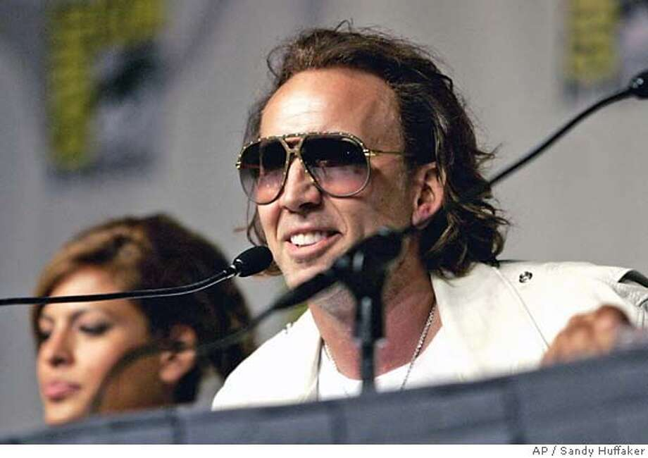 "Actor Nicolas Cage, right, and Eva Mendez promote their new movie ""Ghostrider"" at Comic Con on Saturday, July 22, 2006, in San Diego. (AP Photo/Sandy Huffaker)  Ran on: 07-25-2006  Nicolas Cage plans to portray Liberace, who died in 1987. Photo: SANDY HUFFAKER"