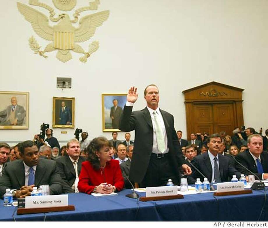 Former Oakland Athletic and Texas Ranger baseball player Mark McGwire is sworn in before testifying at a hearing on Capitol Hill on the use of steroids in professional baseball in Washington Thursday, March 17, 2005. From left, Baltimore Orioles' Sammy Sosa, his interpreter Patricia Rosell, McGwire, Orioles' Rafael Palmiero and Boston Red Sox Curt Schilling. (AP Photo/Gerald Herbert) Photo: GERALD HERBERT