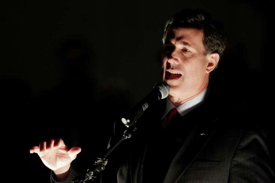 Republican presidential candidate, former Pennsylvania Sen. Rick Santorum, is lit by utility lights as he speaks at an evening outdoor rally at the Washington State History Museum, Monday, Feb. 13, 2012, in Tacoma, Wash. (AP Photo/Ted S. Warren) Photo: Ted S. Warren / AP