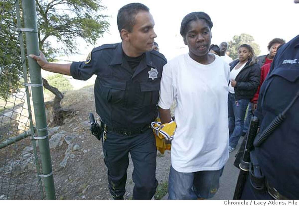 SFPD Officer Lewis Dejesus, from the Bayview Station, makes an arrest for assault after chancing the suspect through the Habor Housing Project, Thursday April 29, 2004. EDITOR NOTE--- The young girl in a minor and goes by the first name of