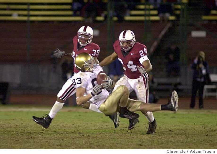 Notre Dame's JeffSamardzija makes first down catch that sets up a second half TD as Trevor Hooper, right, anb T.J. Rushing cover.  The Stanford Cardinal had their last home game of the season and last home game in their stadium vs. Notre Dame. Notre Dame came back in the final minute after Standford TD.  Photo taken on 11/27/05, in Palo Alto Photo: Adam Traum
