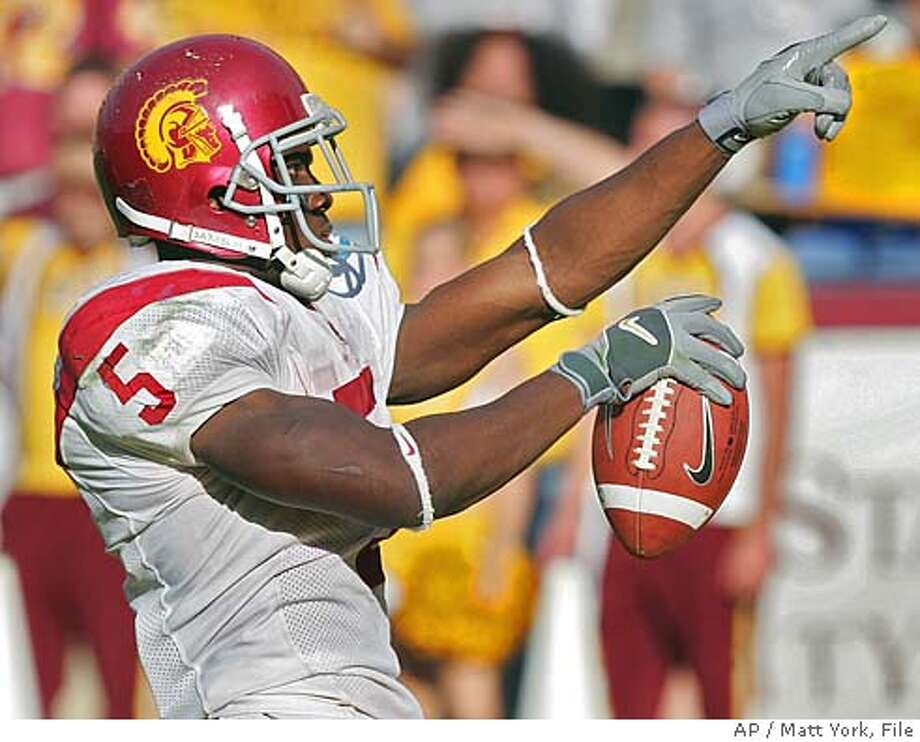 ** FILE ** Southern California running back Reggie Bush celebrates after scoring the game's go-ahead touchdown against Arizona State during the fourth quarter in this, Oct. 1, 2005 photo, at Sun Devil Stadium in Tempe, Ariz. Bush set out last summer to become a complete running back, not just a guy with sprinter's speed who could attack the flanks of a defense. He's accomplished that, and a lot more for top-ranked USC, making him the apparent front-runner for the Heisman Trophy. (AP Photo/Matt York) Ran on: 12-11-2005 Ran on: 12-11-2005 Photo: MATT YORK