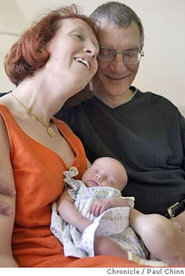 Alette Coble-Temple and her husband Bob Temple snuggle with their new adopted daughter Katie at their home on 4/27/04 in Walnut Creek. PAUL CHINN/The Chronicle Photo: PAUL CHINN
